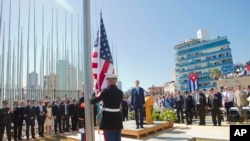 Secretary of State John Kerry and others watch as U.S. Marines raise the U.S. flag over the newly reopened embassy in Havana, Cuba.