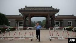 北京郊區秦城監獄入口處,一名女警員試圖阻止記者拍照。