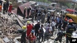 Regu pemadam kebakaran dan tim SAR mencari korban di sekitar lokasi meledaknya bom di Bab al-Muadham, Baghdad, Irak (4/6).