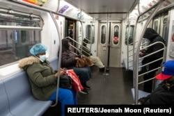 Warga di dalam kereta (subway) mengenakan masker di stasiun kereta api Times Square di tengah pandemi Covid-19 di New York City, 17 April 2020. (Foto: dok).