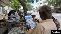 FILE - People read newspapers in the streets of Somalia's capital Mogadishu May 3, 2011. Popular Somali newspaper Xog-Ogaal remains closed and its editor in detention for a second day.