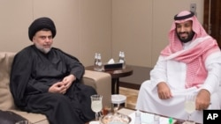 Shiite cleric Muqtada al-Sadr, left, meets with Saudi Crown Prince Mohammed bin Salman in Jiddah, Saudi Arabia, July 30, 2017.