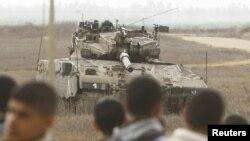 Warga Palestina berdiri di dekat pagar perbatasan Israel-Palestina di Jalur Gaza, memandangi tank Israel yang tengah berjaga di wilayah itu (Foto: dok). Dilaporkan dua orang Palestina terluka terkena tembakan di Gaza tengah (23/12).
