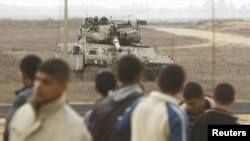 Palestinians stand close to the fence as an Israeli tank is seen on the border between Israel and southern Gaza Strip, November 23, 2012.