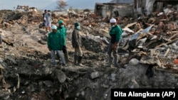 In this October 2, 2018 photo, volunteers of the humanitarian wing of the Islamic Defenders Front examine the damage caused by the earthquake and liquefaction at Balaroa neighborhood in Palu, Central Sulawesi, Indonesia.
