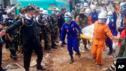 In this photo provided by Preah Sihanouk Provincial Authority, rescuers carry the body of a victim at the site of a building collapse, Monday, June 24, 2019, in Preah Sihanouk province, Cambodia.