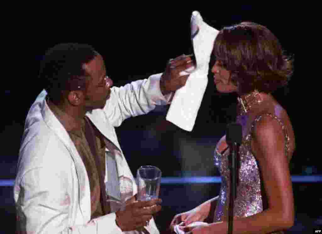 """Entertainer Bobby Brown wipes the brow of wife Whitney Houston during her performance at the Shrine Auditorium in Los Angeles, Monday, April 10, 2000, during taping of the """"25 Years of #1 Hits: Arista Records' Anniversary Celebration."""" The show, a tribute"""