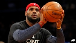 Cleveland Cavaliers forward LeBron James warms up before an NBA basketball game against the Brooklyn Nets at the Barclays Center in New York, Dec. 8, 2014.
