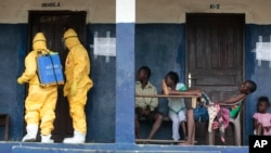Residents of a West African village watch as members of a response team disinfect an area as they pick up suspected Ebola patients that had been quarantined, Sept. 30, 2014.