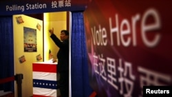 2012年11月7日,在美国驻北京大使馆组织的模拟投票中,一位客人投下自己的一票。这一票可能是支持奥巴马,也可能是支持罗姆尼。