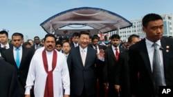 2014年9月17日,习近平主席访问斯里兰卡。图为习近平和斯里兰卡总统拉贾帕克萨(身穿白衣者)在启动科伦坡的港口城项目后一起行走(资料照)