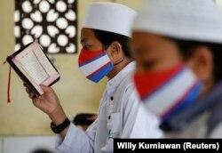 Siswa Muslim mengenakan masker wajah di tengah penyebaran COVID-19, saat membaca Alquran di Masjid Al-Kautsar Daarul Qur'an selama bulan suci Ramadhan, di Bogor, Jawa Barat, 9 Mei 2020 . (Foto: Reuters/Willy Kurniawan)