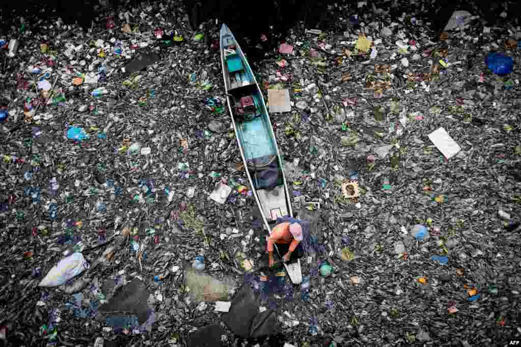 A worker collects garbage from the Marilao River in Bulacan, north of Manila, the Philippines.