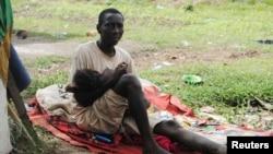 Penderita Ebola, James Flomo menggendong anaknya di Monrovia, Liberia, setelah istri James meninggal akibat ebola tiga hari sebelumnya (foto: dok).