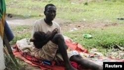 Một người đàn ông ở Monrovia bị nghi nhiễm Ebola ngồi ôm con gái sau khi vợ ông qua đời 3 ngày trước đó vì Ebola.