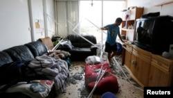 Seorang warga Israel di kota Ashkelon, memeriksa apartemennya yang rusak akibat serangan roket dari Gaza (foto: dok).