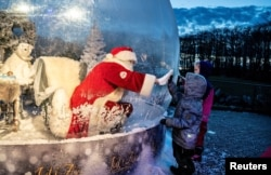 """A person dressed as a Santa Claus meets with children while sitting in a """"Santa Claus bubble"""" as he opens Christmas season at Aalborg Zoo, amid the coronavirus outbreak, in Aalborg, Denmark."""