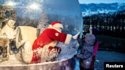 "A person dressed as a Santa Claus meets with children while sitting in a ""Santa Claus bubble"" as he opens Christmas season at Aalborg Zoo, amid the coronavirus outbreak, in Aalborg, Denmark."
