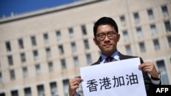 Hong Kong exiled pro-democracy activist Nathan Law holds a placard outside the Italian Foreign Ministry headquarter as he speaks to media, during the meeting between Italian Foreign Minister and his Chinese counterpart in Rome on August 25, 2020