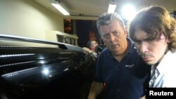 Ray Whelan (kiri), direktur Match Services, tiba di kantor polisi setelah ditangkap di Rio de Janeiro (7/7).