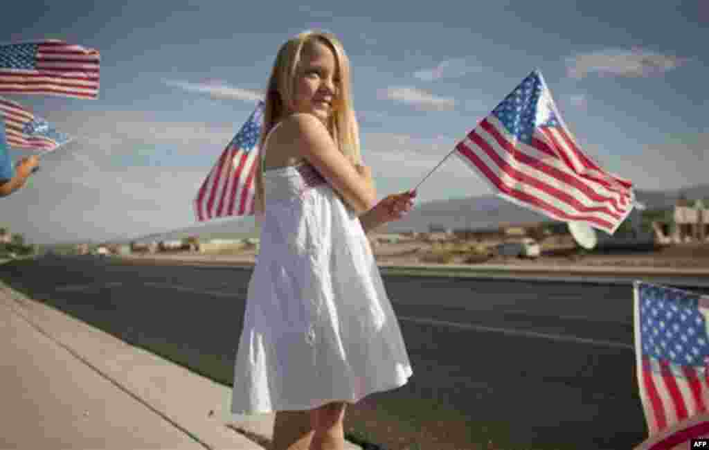 Eight-year-old Madilynn Hallenback waves American flags along state Highway 160 to commemorate the 10th anniversary of the Sept. 11 attacks Sunday, Sept. 11, 2011, in Pahrump, Nev. (AP Photo/Julie Jacobson)