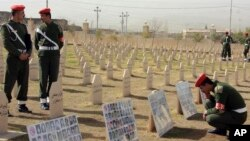 Kurdish soldiers stand in the graveyard for the victims of Halabja massacre, with photos of some of the victims, on its 20th anniversary in Halabja, Iraq, Sunday, March 16, 2008. Some 5,600 people were killed when Saddam Hussein ordered the attack in Ha