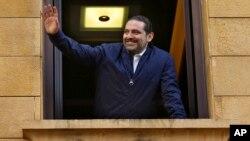 PM Lebanon Saad Hariri melambai kepada pendukungnya dari jendela rumahnya di Beirut, Lebanon, Rabu (22/11).