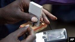 一位肯尼亚的电气工程学生在显示与自行车相连接的充电器如何为手机充电