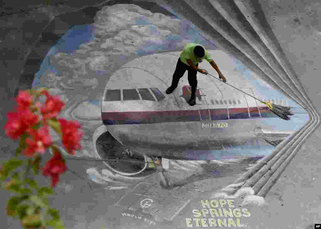 "A school utility worker mops a mural depicting the missing Malaysia Airlines Flight 370 at the Benigno ""Ninoy"" Aquino High School campus at Makati city east of Manila, Philippines."