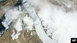 Esta imagen de satélite proporcionada por la NASA muestra el enorme témpano desprendido del glaciar en Groenlandia.