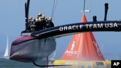 Oracle Team USA crosses the finish line during the 18th race of the America's Cup sailing event against Emirates Team New Zealand, Sept. 24, 2013, in San Francisco.
