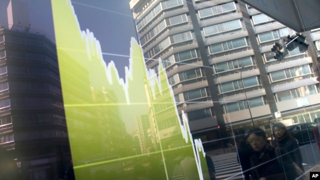 Pedestrians are reflected in an electronic stock chart showing Japan's Nikkei 225 at a securities firm in Tokyo, Tuesday, Feb. 9, 2016.