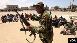 Tentara oposisi pemerintah Libya mengajarkan cara penggunaan senjata pada relawan di Benghazi.
