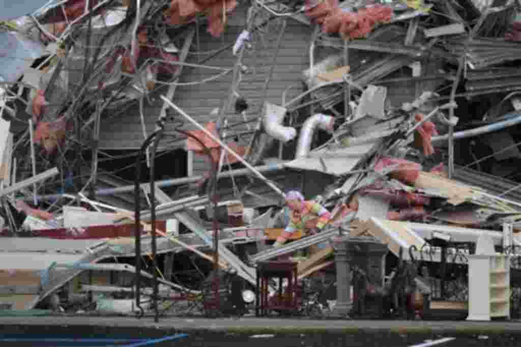 Una mujer contempla la destrucción de una antigua oficina de T Mobile después del tornado.