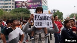 "A man carrying a girl on his shoulder holds up a paper reading ""PX (paraxylene petrochemicals) get out of Maoming, return us clean land"", as demonstrators gather to protest against a chemical plant project, near the city government building in Maoming, Gu"