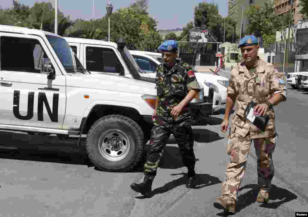 Members of the United Nations observers mission in Syria, who have left their bases in the province of Homs in Central Syria, return to their hotel in Damascus August 20, 2012.