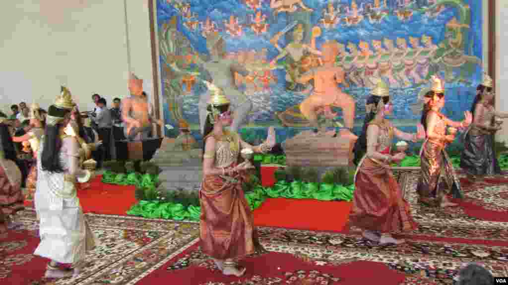 Dancers perform near three pieces of the 10th century Cambodian sandstone statues from the United States, during a handover ceremony at the Council of Ministers, in Phnom Penh, June, 3, 2014. (VOA Khmer)