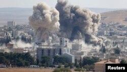 Un nuage de fumée s'élève après les frappes de la coalition internationale menée par les Etats-Unis contre une position de l'armée syrienne à Kobane, Syrie, 8 octobre 2014.