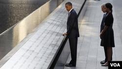 Presiden Obama menyentuh tulisan papan nama korban di lokasi kejadian World Trade Center, New York disaksikan Michalee Obama, mantan presiden AS dan ibu negara George dan Laura Bush (11/9).