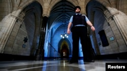 在渥太华国会山庄的国会图书馆入口附近,一名安全警卫在巡逻(2014年10月23日)