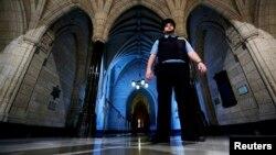 Seorang petugas keamanan berjaga di dekat pintu masuk gedung perpustakan parlemen Kanada di Ottawa, Kamis (23/10).