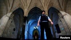 Petugas keamanan berpatroli di aula dekat pintu masuk perpustakaan gedung parlemen di Kanada, Ottawa (23/10). (Reuters/Chris Wattie)