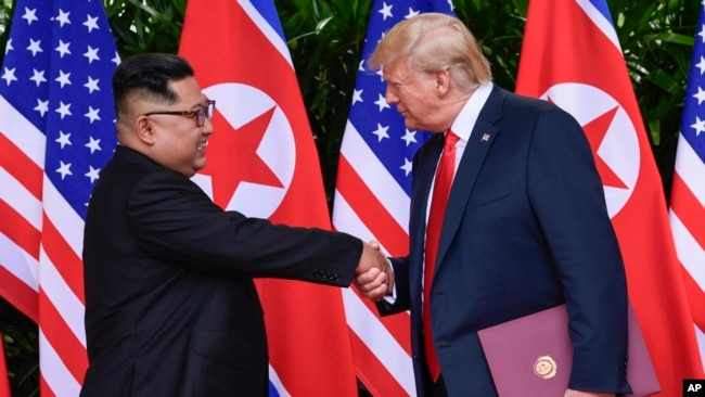 FILE - In this June 12, 2018, file photo, North Korea leader Kim Jong Un, left, and U.S. President Donald Trump shake hands at the conclusion of their meetings at the Capella resort on Sentosa Island in Singapore.