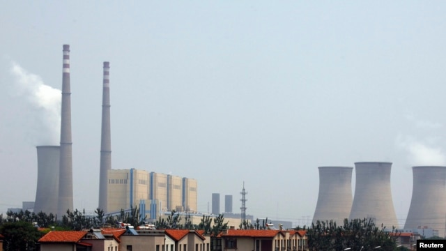 The cooling towers and chimneys from a coal-burning power station can be seen behind a man standing next to his car in a newly constructed residential area in Beijing, (File photo).