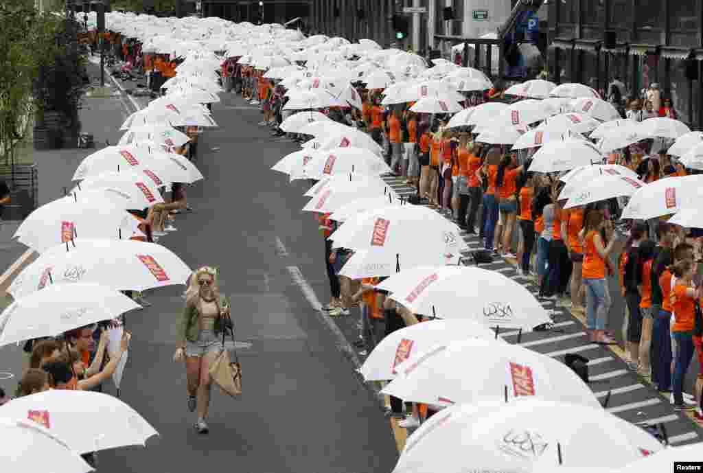 Graduates hold umbrellas during graduation, as part of a mass dance with more than 4,000 graduates dancing in Ljubljana and other Slovenian towns, according to organizers.