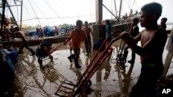 Các công nhân di trú làm việc tại một chợ cá trong tỉnh Samut Sakhon, nằm về hướng tây thủ đô Bankok, 20/6/14