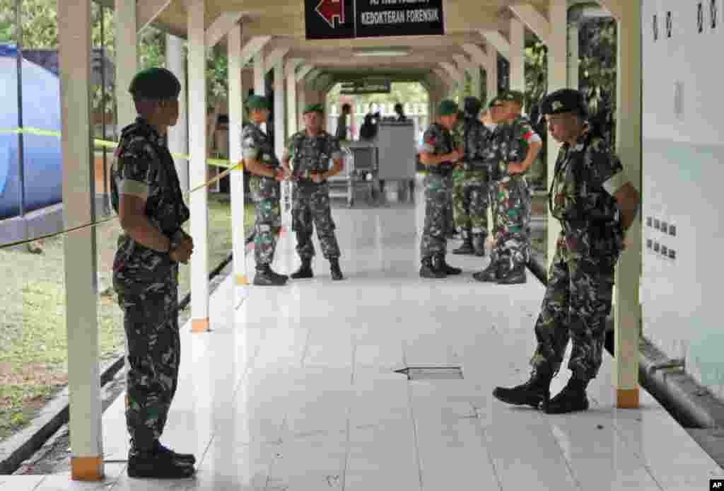 Indonesian soldiers stand guard in a hallway at the police hospital where the bodies of the victims of AirAsia Flight 8501 are brought into for identification process, in Surabaya, East Java, Indonesia, Dec. 31, 2014.