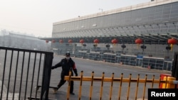 一名保安人员星期天1月26日正在北京四惠长途车站关上铁门。