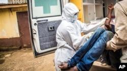 Zdravstveni radnici ubacuju pacijenta koji ima ebolu u kola hitne pomoći