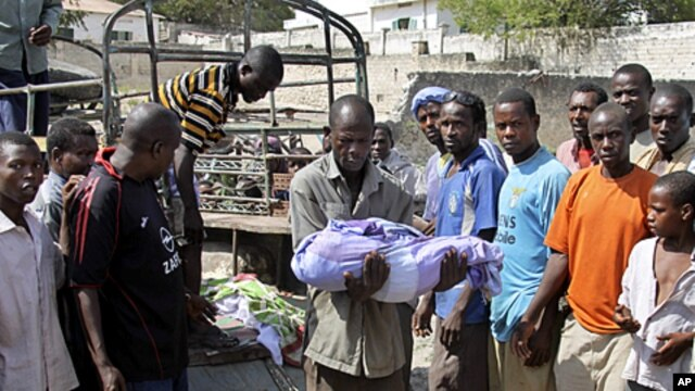 A Somali man carries the body of a one year old child who was killed by a mortar shell that slammed into a family's house Sunday night, to a grave in the capital Mogadishu, Somalia, March 19, 2012.